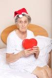 Dame âgée s'est habillée dans le chapeau de Santa avec le coeur rouge dans des ses mains Photos libres de droits