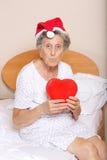 Dame âgée s'est habillée dans le chapeau de Santa avec le coeur rouge dans des ses mains Image stock