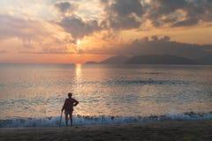Dame âgée seule se tenant sur la plage Nha Trang, Vietnam Image libre de droits