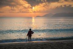 Dame âgée seule se tenant sur la plage Nha Trang, Vietnam Photographie stock