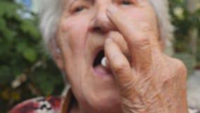 Dame âgée tenant la pilule blanche dans sa main et la prennent Grand-mère mettant le comprimé dans sa bouche blanc médical d'isol banque de vidéos