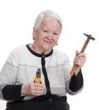 Dame âgée tenant le marteau et les pinces Photographie stock