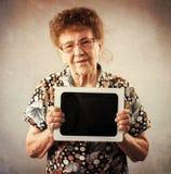 Dame âgée tenant un comprimé dans les mains de Image stock