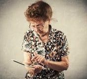 Dame âgée tenant un comprimé dans les mains de Photo stock