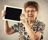 Dame âgée tenant un comprimé dans les mains de Photographie stock libre de droits