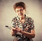 Dame âgée tenant un comprimé dans les mains de Photographie stock