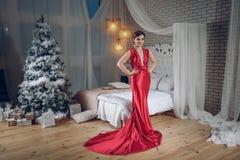 Dame élégante dans la robe de soirée rouge au-dessus du fond d'arbre de Noël dans un intérieur chic ou de luxe la fille va à une  photos libres de droits