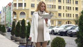 Dame élégante enceinte avec la valise recherchant l'hôtel avec la carte, voyage d'affaires photo stock