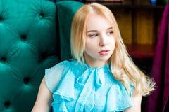 Dame élégante portant la robe bleue se reposant dans la chaise dans la bibliothèque Beauté, mode image libre de droits