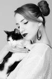 Dame élégante tenant le chat noir et blanc Images libres de droits