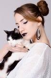 Dame élégante tenant le chat noir et blanc avec les yeux jaunes Images stock