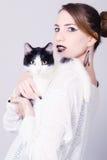Dame élégante tenant le chat noir et blanc avec les yeux jaunes Photographie stock