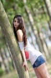 Dame étonnante de brune avec de longs cheveux bouclés, femme se penchant sur l'arbre Images stock