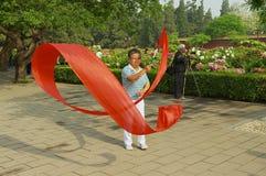 Dame übt traditionelle Gymnastik mit rotem Band in Jingshan-Park in Peking, China Lizenzfreie Stockfotografie