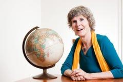 Dame aînée avec une carte de la terre Photographie stock libre de droits