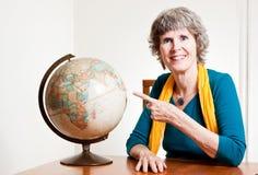 Dame aînée indiquant une carte de la terre Images stock