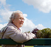 Dame aînée s'asseyant sur le banc de stationnement Photo stock