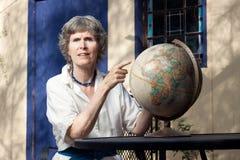 Dame aînée se dirigeant à une carte (globe) Photo stock