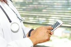 Dame active asiatique de femme tenant le téléphone portable pour communiquer au sujet du travail à l'hôpital image stock