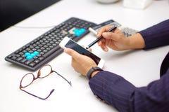 Dame active asiatique de femme tenant le téléphone portable pour communiquer au sujet du travail au bureau moderne image libre de droits