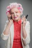 Dame adulte supérieure agréable avec des bigoudis de cheveux utilisant le téléphone portable Images libres de droits