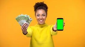 Dame afro-am?ricaine montrant le smartphone et le groupe d'euros, transfert d'argent images libres de droits