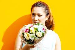 Dame asiatique dans le bouquet de prise de suite de robe Photos stock