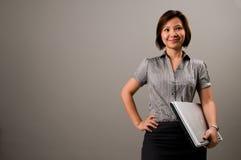 Dame asiatique dans le vêtement d'affaires, retenant un cahier photos libres de droits