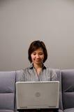 Dame asiatique dans le vêtement d'affaires, utilisant un ordinateur photographie stock libre de droits