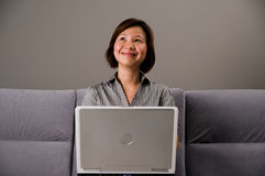 Dame asiatique dans le vêtement d'affaires, utilisant un ordinateur photographie stock