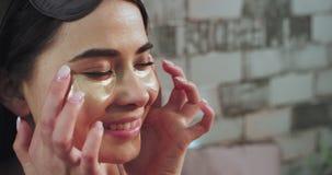 Dame asiatique de détails de plan rapproché belle pendant le matin elle ont une routine de beauté mise sur des caches de visage e banque de vidéos