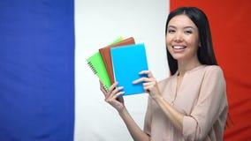 Dame asiatique de sourire montrant des cahiers sur le fond français de drapeau, leçons clips vidéos