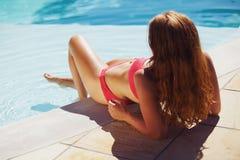 Dame assez jeune appréciant le bain de soleil par la piscine Photos libres de droits