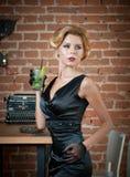 Dame attirante à la mode avec peu de robe et gants noirs se tenant près d'une table dans le restaurant tenant un verre de boisson images stock