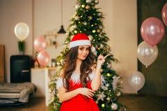 Dame attirante dans le costume d'un Santa Claus New Year, une robe rouge d'écarlate avec les épaules ouvertes et un chapeau, par  photos libres de droits
