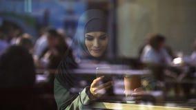 Dame attirante dans le hijab causant au téléphone, libre pour communiquer avec des amis images libres de droits