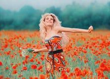 Dame attirante gaie et joyeuse avec les cheveux blonds dans une robe serrée mignonne, courses à travers le champ de pavot, tenant photographie stock