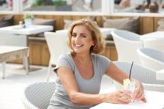 Dame attirante seul s'asseyant dehors avec une boisson de l'eau Photo stock