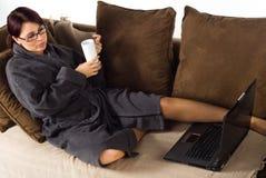 Dame auf der Couch, die mit Kaffee arbeitet Lizenzfreie Stockfotografie