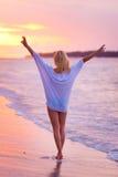 Dame auf sandigem tropischem Strand bei Sonnenuntergang Stockfotos