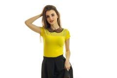 Dame avec du charme de brune dans le costume jaune et noir posant sur l'appareil-photo Image libre de droits