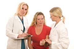 Dame behandelt medizinische Kleidung mit Patienten stockfoto