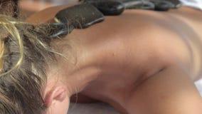 Dame bij de massage van de kuuroordbehandeling Basalt hete stenen met de behandeling van massageoliën HD stock footage