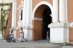 Dame, Blinder neben behindertem Bettler im Rollstuhl am Friedhofs-Tor-Portal Lizenzfreie Stockfotos