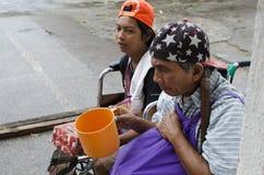 Dame, Blinder neben behindertem Bettler im Rollstuhl am Friedhofs-Tor-Portal Stockfotografie