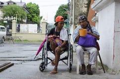 Dame, Blinder neben behindertem Bettler im Rollstuhl am Friedhofs-Tor-Portal Stockbild