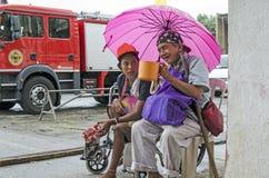 Dame, Blinder neben behindertem Bettler im Rollstuhl am Friedhofs-Tor-Portal mit Regenschirm Lizenzfreies Stockfoto