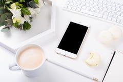 Dame Bloggers bearbeiten Schreibtisch mit frischem Blumenstrauß von Blumen und von macaro Stockfoto