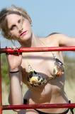 Dame blonde avec le bikini de port de corps mince et sportif ayant l'amusement près d'un parc d'amusement Image libre de droits