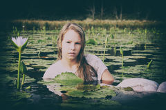 Dame blonde flottant parmi les lillies Photographie stock